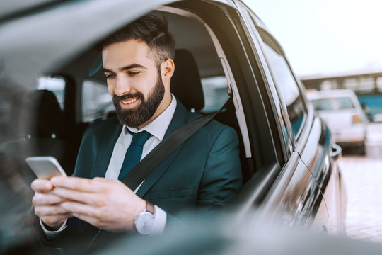 Smiling Caucasian businessman in formal wear using smart phone while sitting in his car on parking lot.