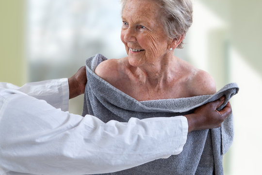 Care giver or nurse assisting elderly woman for showerand drying her