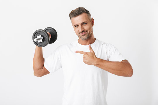Image of european man 30s with bristle wearing casual t-shirt pumping biceps and lifting dumbbell