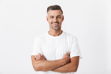 Image of optimistic man 30s with bristle wearing casual t-shirt posing and looking on camera