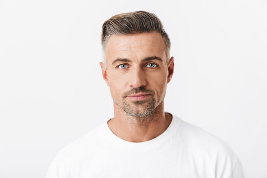 Image of confident man 30s with bristle wearing casual t-shirt posing and looking on camera