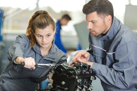auto mechanic guiding a female trainee in garage