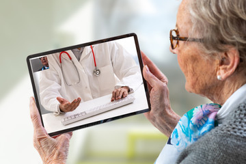 Senior woman consults a e-health doctor with tablet computer sitting in soft chair. In touchscreen,...