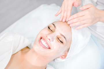 Beautician makes facial massage with mask. Beautiful smiling girl on spa procedure. Facial care. Wall mural