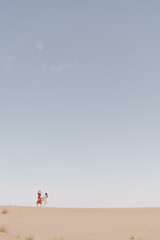 Two happy women walking barefoot in the distance on a sand dune in the Dubai desert