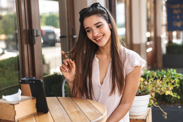 Beautiful young woman sitting at the cafe table outdoors