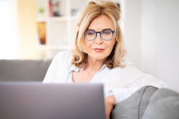 Frau mit Brille zuhause auf der Couch mit laptop