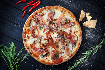 Top view on fresh homemade italian pizza with jamon, pear and walnut. Pizza, cheese, cherry tomato and parsley on dark wooden background with copy space for design. Top view food menu, recipe