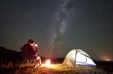 Female hiker having a rest at summer night camping in the mountains beside campfire and glowing tourist tent. Young woman sitting on chair, taking picture of night sky full of stars and Milky way.