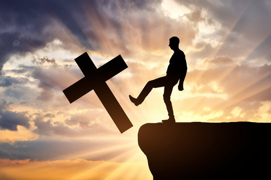 Man atheist pushes the symbol of christian cross into the cliff