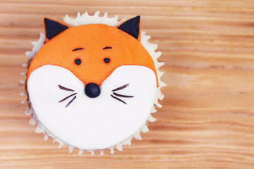 Decorated cupcake on wooden background