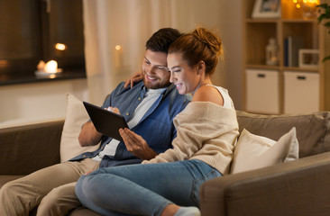 technology, internet and people concept - happy couple using tablet computer at home in evening