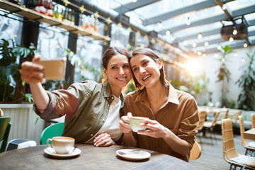 Happy attractive young women in casual shirts sitting at table in coffee shop and photographing together while drinking coffee