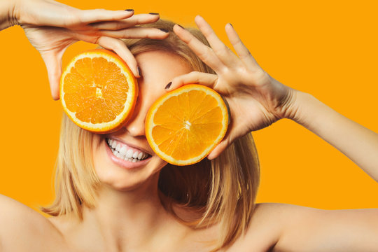 beautiful stylish girl holding orange smiling and looking at camera isolated