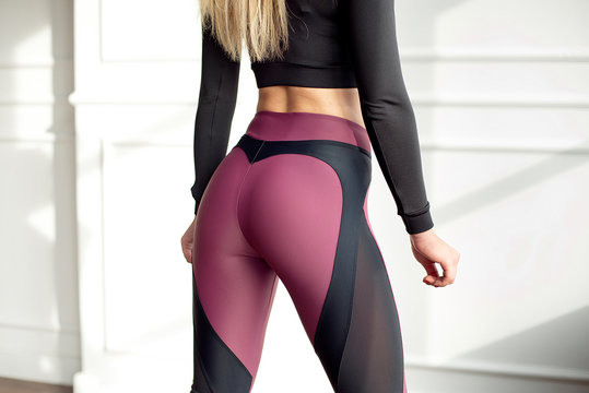 Young slim woman with an athletic body long blonde hair wearing in black sports sportswear top and leggings standing in bright yoga room with big panoramic window preparing before training health-life