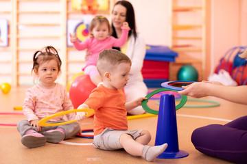 Nursery babies group doing sport in gym