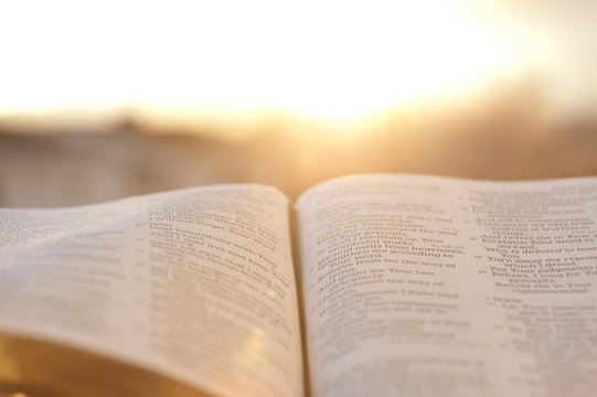 Open Bible with bright sunset in the background. Close-up. Horizontal shot.