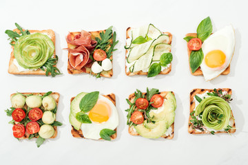 Top view of toasts with cut vegetables and prosciutto on white surface