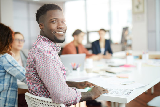 Portrait of young African-American man smiling at camera while sitting at table in business meeting, copy space