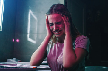 Drug obsession and pain. Drug addict holds hands on her hand and is going crazy near drugs. Alone drug addicted woman with smeared makeup cries in night club's toilet. Find strength to fight with drug