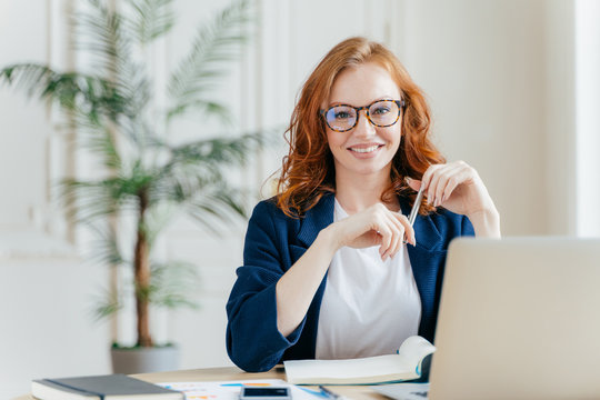 Portrait of happy redhaired woman employee in optical glasses, has satisfied expression, works with modern gadgets, waits for meeting with colleague, prepares accounting report, sits in own cabinet