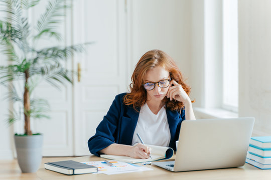 Serious confident female entrepreneur in formal clothes writes down information while watches business webinar, notes main ideas, sits at work place in front of opened computer makes notes for startup