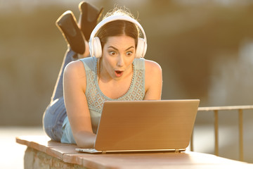 Surprised girl with headphones checking laptop