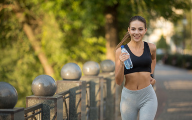 Friendly female jogger running in morning with water