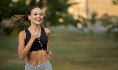Happy active woman running and listening to music Wall mural