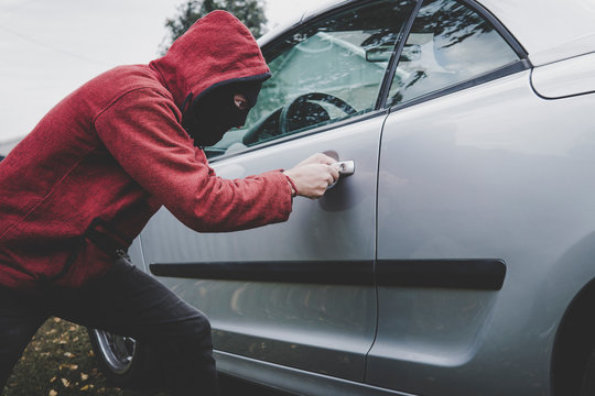 Criminal in black balaclava and hoodie opens somebody's vehicle with skeleton key. Car breaking by unknown male with hidden face. Young man picks automobile lock to get inside. Forcing the car door