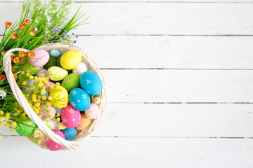 Basket with easter eggs on rustic wooden table. Top view.