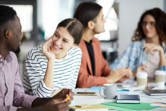 Portrait of smiling young woman talking to African-American colleague during meeting in office, copy space