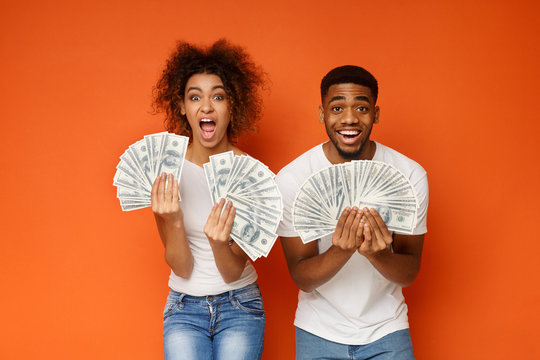 Shocked and happy black guy and girl holding lots of money