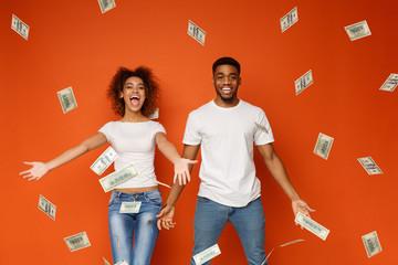 Young black couple enjoying money banknotes shower