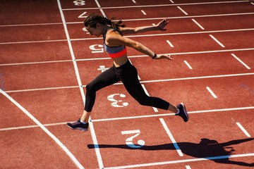 Side view of female teen athlete in sports bra and tights successfully finishing race on track at...