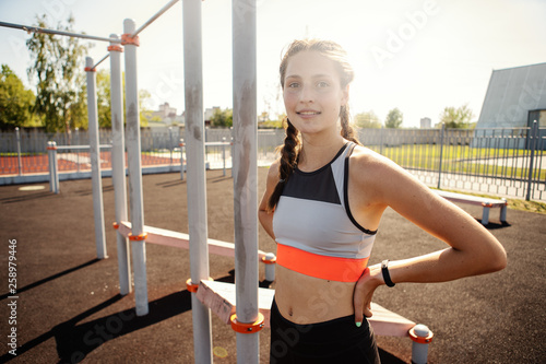 Fit teenage girl in sportswear with smartwatch on her wrist and