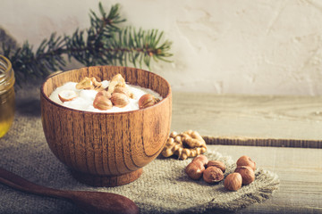 Wooden bowl with yogurt and nuts on burlap napkin on rustic wooden table.
