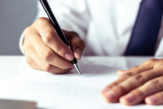 Businessman signing a document in office