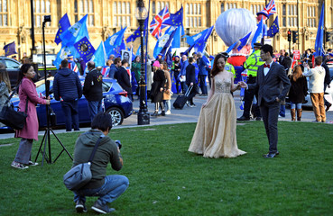 A couple poses for wedding photographs in front of anti-Brexit and pro-Brexit supporters outside the Houses of Parliament in London
