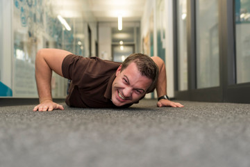 Businessman doing push-ups on office floor
