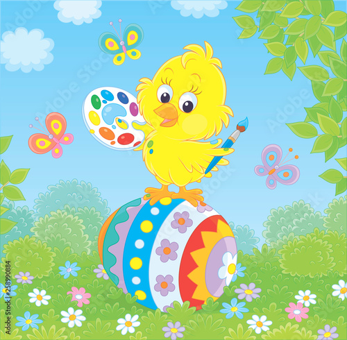 Little yellow chick coloring an Easter egg among flowers on ...