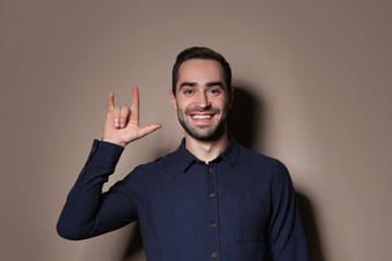 Man showing I LOVE YOU gesture in sign language on color background