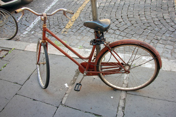 old rusty bike parked at the post and chained with a lock on the street