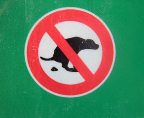 dog walking is prohibited, a red round sign with a crossed-out image of a pooping dog in black on a white and green background close-up