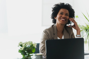 Happy smiling african-american business woman working on laptop at office, using smart phone. Businesswoman sitting at her working place Wall mural