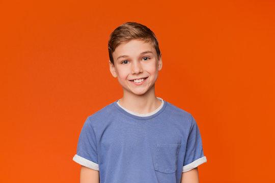 Portrait of young boy on orange background