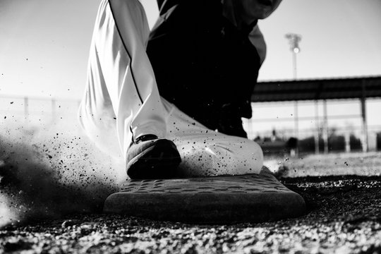Baseball player sliding into base closeup.  Sports action image in black and white.