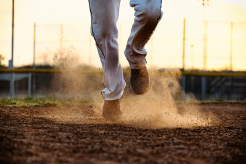 Baseball player feet running to base on field, dirt and dust moving from action of athlete.