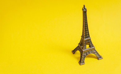 Fotobehang Eiffeltoren photo of Eiffel Tower shaped souvenir on the wonderful yellow studio background
