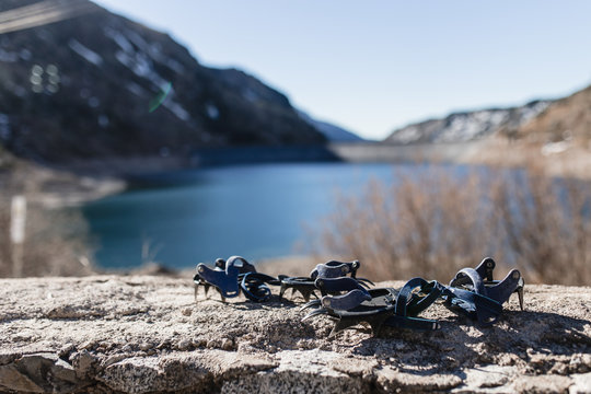Detail of crampons on a rocks a lake backside
